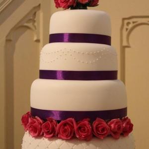 Fuchsia pink roses and purple wedding cake